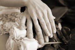 Hände mit Eheringen auf Brautblumenstrauß Sepia Stockfotos