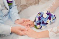 Hände mit Eheringen und Hochzeitsblumenstrauß Stockbilder