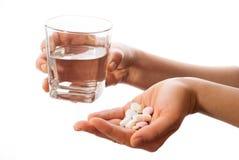 Hände mit einem Glas Wasser und Medizin Lizenzfreie Stockbilder
