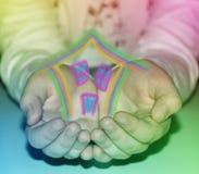 Hände mit einem Haus in der Regenbogenfarbe lizenzfreies stockfoto