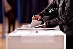 Hände mit einem Stempel, der eine Abstimmung abgibt Lizenzfreie Stockfotografie