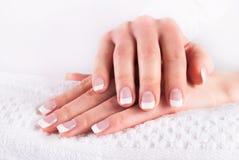 Hände mit französischen Nägeln maniküren auf weißem Tuch Stockbild