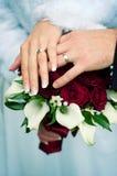 Hände mit Hochzeitsgoldringen und -blumen lizenzfreies stockbild