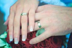 Hände mit Hochzeitsgoldringen und -blumen stockfotografie