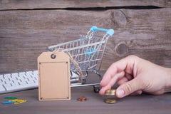 Hände mit Kreditkarte auf Computertastatur Kauf des Warenkorbes mit einem leeren Preis auf einem dunklen hölzernen Hintergrund Stockfoto
