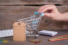 Hände mit Kreditkarte auf Computertastatur Kauf des Warenkorbes mit einem leeren Preis auf einem dunklen hölzernen Hintergrund Lizenzfreies Stockbild