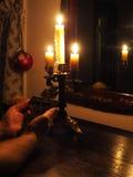 Hände mit Kruzifix und Kerzen in der Dunkelheit Stockfoto