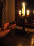 Hände mit Kruzifix und Kerzen in der Dunkelheit Lizenzfreies Stockfoto