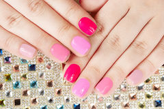 Hände mit manikürten Nägeln auf buntem Kristallhintergrund Stockfotografie