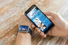 Hände mit Nachrichtenwebseite auf intelligentem Telefon und Uhr Stockbilder