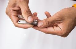 Hände mit Nagelscherer Stockbilder
