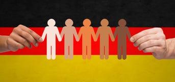 Hände mit Papierleutepiktogramm über deutscher Flagge Lizenzfreie Stockfotos