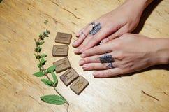 Hände mit Ringen, Runen und Minze stockfotos