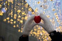 Hände mit rotem Herzen auf dem Schnee stockfotografie