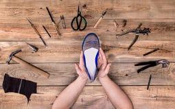 Hände mit Schuh Stockfoto