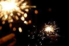 Hände mit Sparklers in der Dunkelheit Lizenzfreie Stockfotos