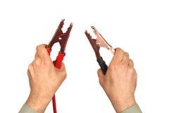 Hände mit Starthilfekabeln auf Weiß Stockfotografie