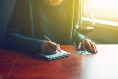 Hände mit Stift und Glas Weinschreiben Lizenzfreie Stockfotos