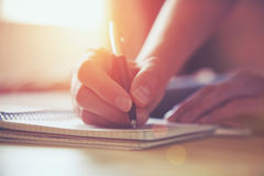 Hände mit Stiftschreiben auf Notizbuch Lizenzfreies Stockfoto