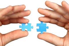 Hände mit zwei Puzzlespielen lizenzfreie stockfotografie