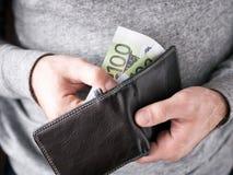 Hände nehmen Euro von der Geldbörse heraus Stockbild