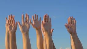 Hände oben auf Hintergrund des blauen Himmels stock video footage