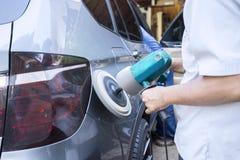 Hände polieren ein Auto mit Poliermaschine Lizenzfreie Stockfotos
