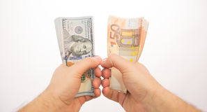 Hände Pov zwei, welche die Dollar und Euros lokalisiert halten Stockfotografie