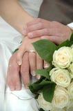 Hände, Ringe und Blumenstrauß Stockfotografie