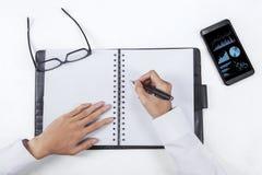 Hände schreiben auf Tagesordnungsbuch Lizenzfreie Stockfotografie