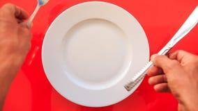 Hände setzten Gabel-Messer horizontal auf Platte auf roter Tabelle stock footage