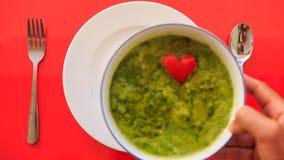 Hände setzten Schüssel Suppe, um Gabel-Löffel auf roter Tabelle in der Nähe zu überziehen