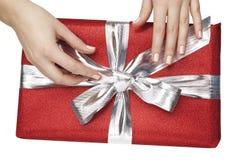 Hände sind Öffnung/Binden eines Farbbands eines roten Geschenks Stockfotografie