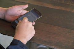 Hände spielen Telefon auf dem Tisch stockfotografie