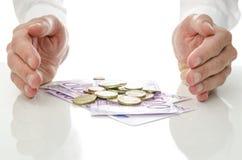Hände um Euromünzen und Banknoten Stockbild