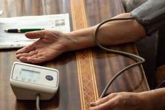 Hände und ein messender Druck des Gerätes auf dem Tisch, ein Stück von p Stockfotos