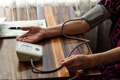 Hände und ein messender Druck des Gerätes auf dem Tisch, ein Stück von p Stockfotografie