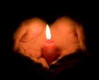 Hände und eine brennende Kerze Lizenzfreie Stockbilder
