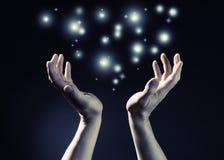 Hände und Glühenleuchte Stockbild