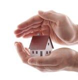 Hände und kleines Haus über Weiß lizenzfreies stockfoto