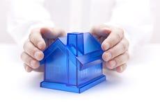 Hände und kleines Haus über Weiß Stockfotografie