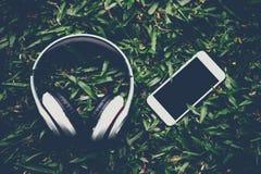 Hände und Kopfhörer werden neben einander in grüne gras gelegt stockbild