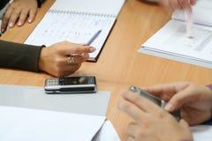 Hände und Mobiles im Büro Lizenzfreie Stockfotos