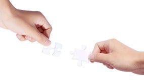 Hände und Puzzlespiel Stockbild