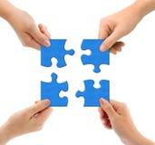 Hände und Puzzlespiel Stockfotografie