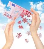 Hände und Puzzlespiel aus dem Geld EURO heraus Stockfotos