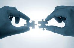 Hände und Puzzlespielstücke im Blau Stockbild