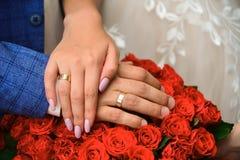 Hände und Ringe auf Hochzeit bouque stockfotos