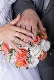 Hände und Ringe auf Hochzeitsblumenstrauß Stockfoto