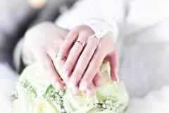 Hände und Ringe auf Hochzeitsblumenstrauß Lizenzfreies Stockbild
